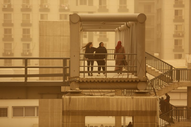 Pedestrians cross a bridge during a sandstorm in Cairo, Egypt, Wednesday, Jan. 16, 2019 as a thick sandstorm cloaked parts of the Middle East. (AP Photo/Amr Nabil)