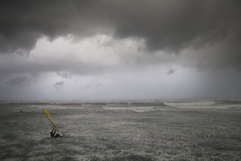 Wind surfers ride on waves in the Mediterranean Sea in Tel Aviv, Israel, Wednesday, Jan. 16, 2019. A harsh weather front brought sandstorms, hail and rain to parts of the Middle East, with visibility down in The Egyptian capital as an orange cloud of dust blocked out the sky. (AP Photo/Oded Balilty)