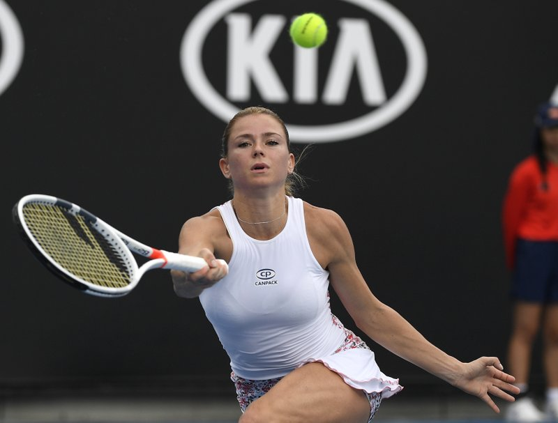 Italy's Camila Giorgi makes a forehand return to Poland's Iga Swiatek during their second round match at the Australian Open tennis championships in Melbourne, Australia, Thursday, Jan. (AP Photo/Andy Brownbill)