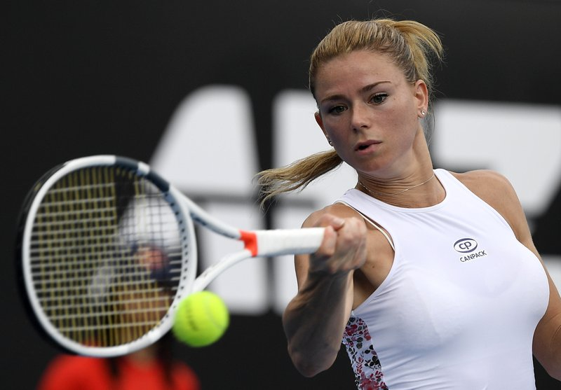 Italy's Camila Giorgi hits a forehand return to Poland's Iga Swiatek during their second round match at the Australian Open tennis championships in Melbourne, Australia, Thursday, Jan. (AP Photo/Andy Brownbill)