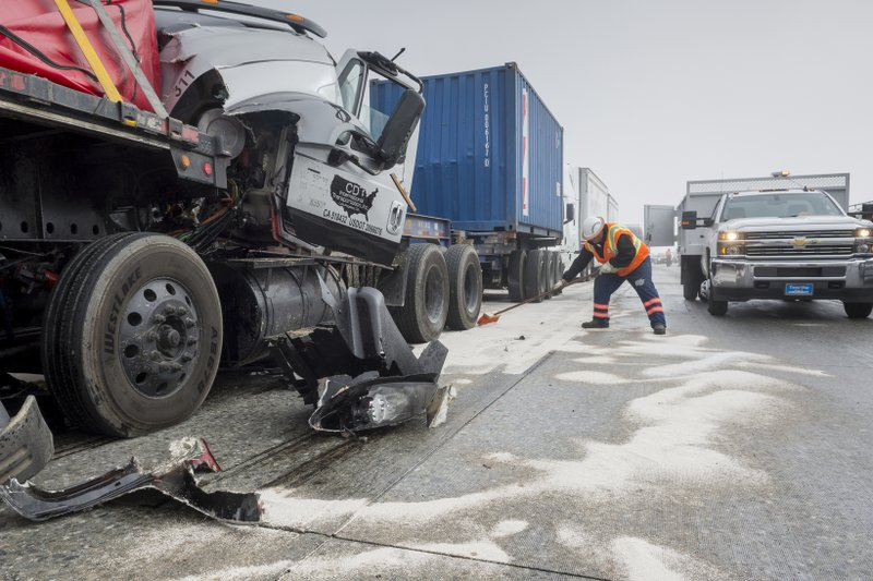 A Caltrans worker covers spilled fuel and liquids with absorbent while cleaning up after a multi-car collision along a foggy Interstate 15 in the Cajon Pass near Hesperia Calif. (James Quigg/The Daily Press via AP)