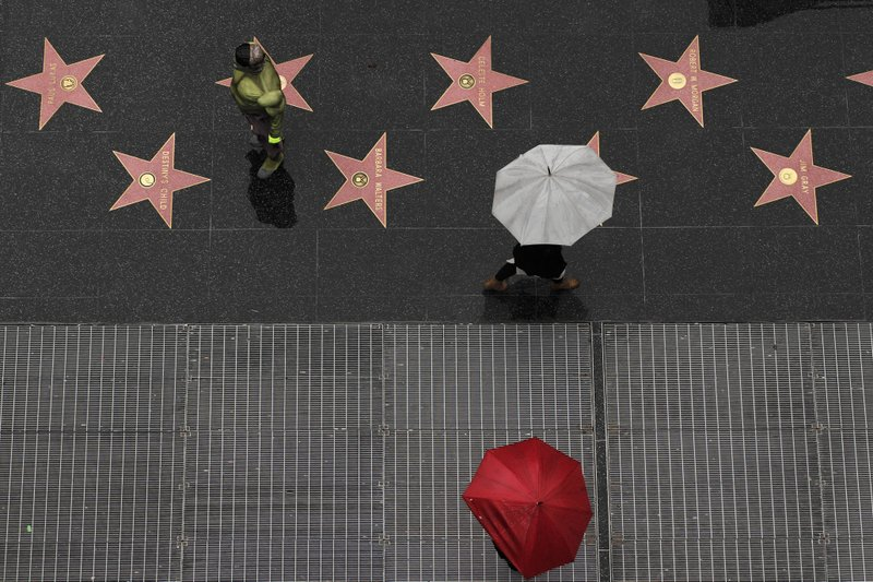 A superhero impersonator stands on the Hollywood Walk of Fame as it rains Wednesday, Jan. 16, 2019, in the Hollywood section of Los Angeles. (AP Photo/Jae C. Hong)