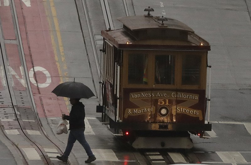 A pedestrian walks in the rain in front of a cable car in San Francisco, Wednesday, Jan. 16, 2019. A series of storms dropped rain up and down the state and snow in mountain regions this week, but the latest storm could be the strongest that Northern California has seen so far this year. (AP Photo/Jeff Chiu)