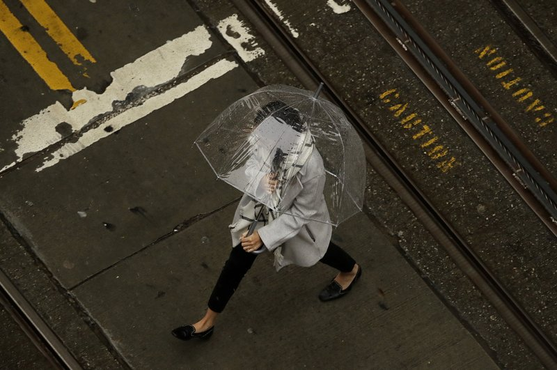 A woman walks in the rain while crossing an intersection in San Francisco, Wednesday, Jan. 16, 2019. A series of storms dropped rain up and down the state and snow in mountain regions this week, but the latest storm could be the strongest that Northern California has seen so far this year. (AP Photo/Jeff Chiu)