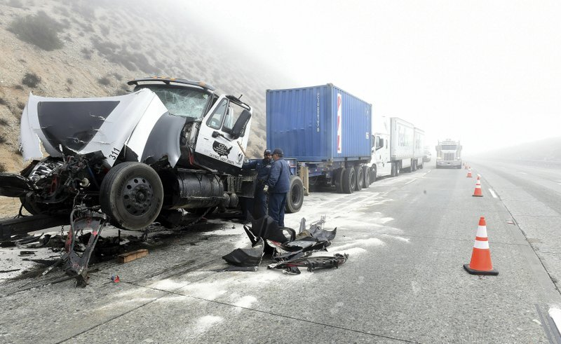 Crews work to clear the roadway after a multi-vehicle collision along a foggy Interstate 15 in the Cajon Pass near Hesperia Calif. (Will Lester/The Orange County Register via AP)