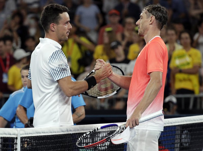 Spain's Roberto Bautista Agut, left, is congratulated by Australia's John Millman after winning their second round match at the Australian Open tennis championships in Melbourne, Australia, Wednesday, Jan. (AP Photo/Kin Cheung)