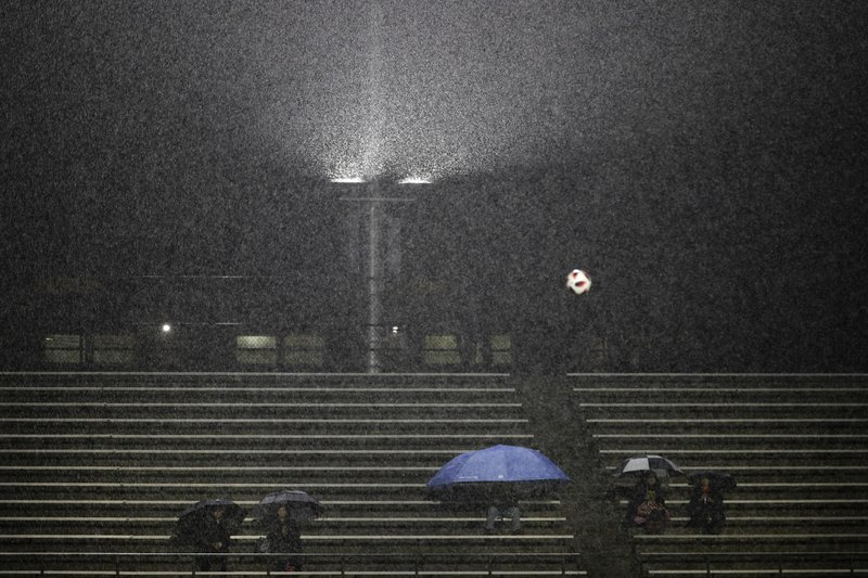 Fans watch a high school soccer match under rain Wednesday, Jan. 16, 2019, in La Habra, Calif. Another Pacific storm is bearing down on California, bringing a threat of mudslides to the site of the deadliest wildfire in state history and a rare blizzard warning in the Sierra Nevada. (AP Photo/Jae C. Hong)