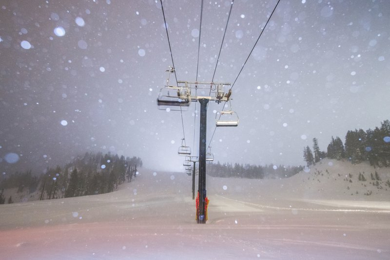 This photo provided by Mammoth Mountain Ski Area shows fresh snow fall over one of the chair lifts at Mammoth Mountain Ski Area in Mammoth Lakes, Calif. (Peter Morning/Mammoth Mountain Ski Area via AP)