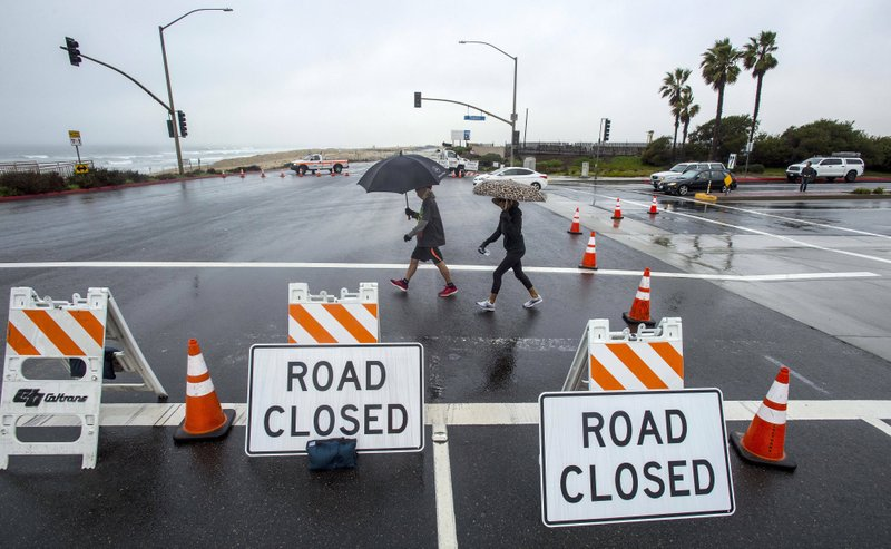 People out for a morning walk cross Pacific Coast Highway at Seapoint Street in Huntington Beach as Caltrans closes PCH to Warner Avenue due to flooding from the storms that have moved through Orange County on Wednesday, January 16, 2019. (Mark Rightmire/The Orange County Register via AP)