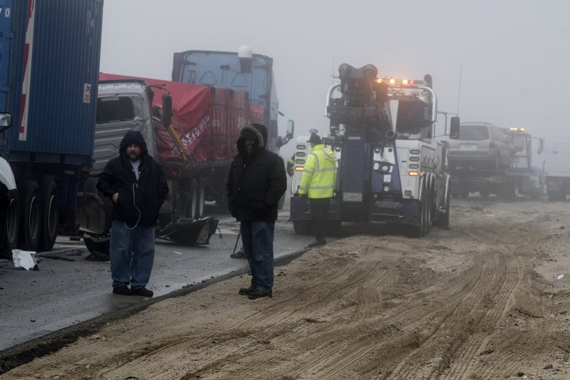 Truck drivers watch damaged semitrailers get removed from the scene of a multi-car collision in the Cajon Pass near Hesperia, Calif. (James Quigg/The Daily Press via AP)