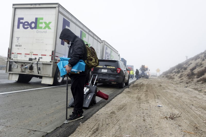A collision victim waits for transportation after his car was severely damaged in a multi-car collision in the Cajon Pass near Hesperia, Calif. (James Quigg/The Daily Press via AP)