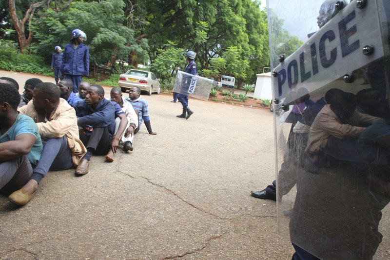 A policeman stands guard as some of the people arrested during demonstrations over the hike in fuel prices, make their court appearance at the magistrates courts in Harare, Zimbabwe, Wednesday, Jan,16, 2019. (AP Photo/Tsvangirayi Mukwazhi)