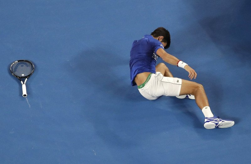 Serbias Novak Djokovic falls during his second round match against France's Jo-Wilfried Tsonga at the Australian Open tennis championships in Melbourne, Australia, Thursday, Jan. (AP Photo/Mark Schiefelbein)