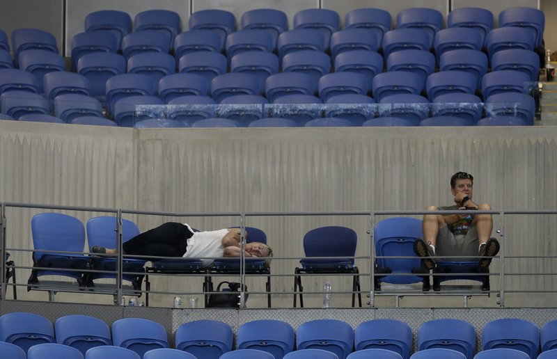 A spectator sleeps at Margaret Court Arena as Spain's Garbine Muguruza and Britain's Johanna Konta play their second round match at the Australian Open tennis championships in Melbourne, Australia, Friday, Jan. (AP Photo/Mark Baker)