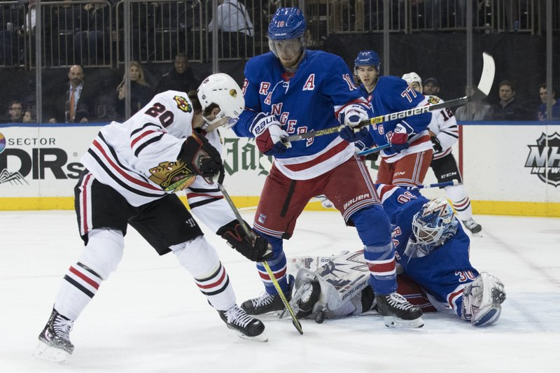 New York Rangers goaltender Henrik Lundqvist (30) and defenseman Marc Staal (18) defend against Chicago Blackhawks left wing Brandon Saad (20) during the first period of an NHL hockey game Thursday, Jan. (AP Photo/Mary Altaffer)
