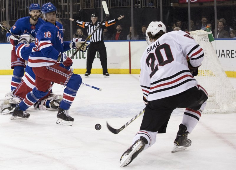 Chicago Blackhawks left wing Brandon Saad (20) shoots for a goal past New York Rangers defenseman Marc Staal (18) during the first period of an NHL hockey game Thursday, Jan. (AP Photo/Mary Altaffer)
