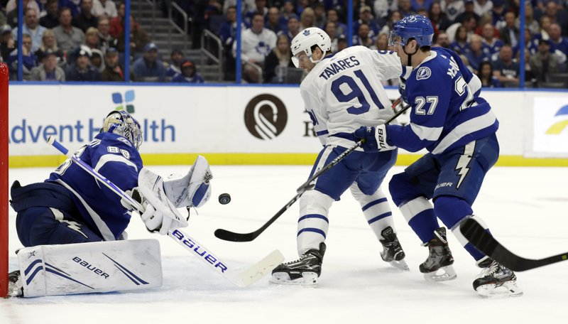 Tampa Bay Lightning goaltender Andrei Vasilevskiy (88) reaches for a shot by Toronto Maple Leafs center John Tavares (91) as defenseman Ryan McDonagh (27) closes in during the first period of an NHL hockey game, Thursday, Jan. (AP Photo/Chris O'Meara)