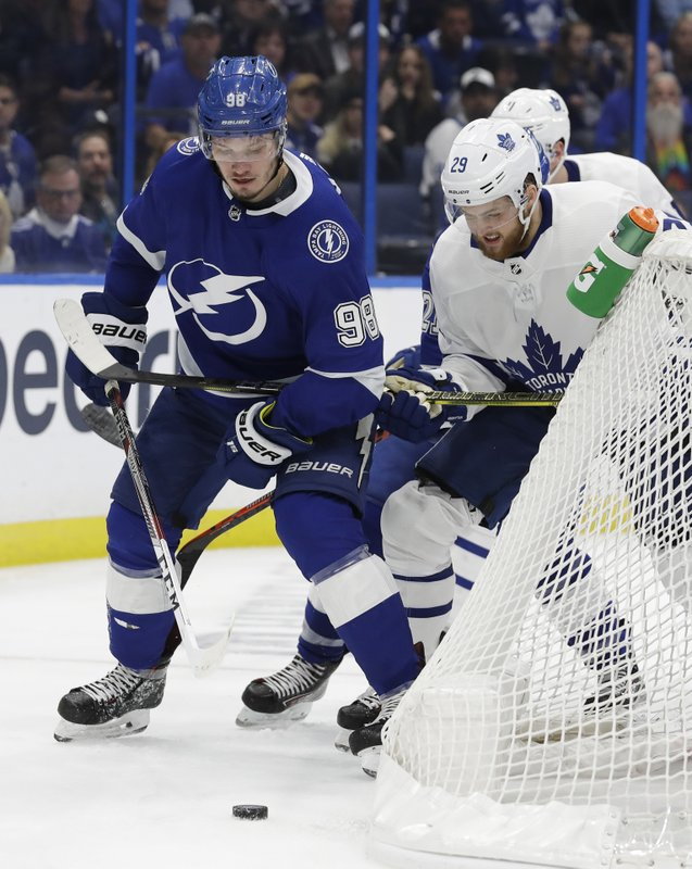 Tampa Bay Lightning defenseman Mikhail Sergachev (98) battles with Toronto Maple Leafs right wing William Nylander (29) for a loose puck behind the net during the third period of an NHL hockey game, Thursday, Jan. (AP Photo/Chris O'Meara)
