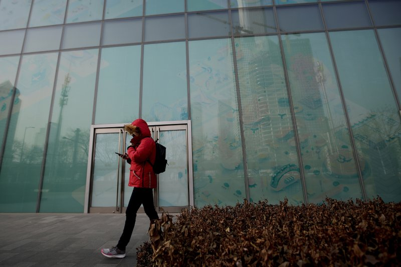 In this Jan. 12, 2019, photo, a man walks by a vacant retail space window panels at the Central Business District in Beijing. (AP Photo/Andy Wong)