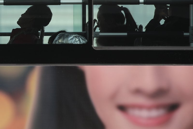 In this Jan. 12, 2019, photo, commuters ride on a bus with a smiling face advertisement at the Central Business District in Beijing. (AP Photo/Andy Wong)