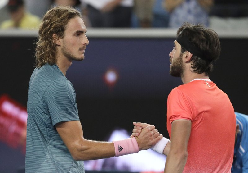 Greece's Stefanos Tsitsipas, left, is congratulated by Georgia's Nikoloz Basilashvili after winning their third round match at the Australian Open tennis championships in Melbourne, Australia, Friday, Jan. (AP Photo/Mark Schiefelbein)