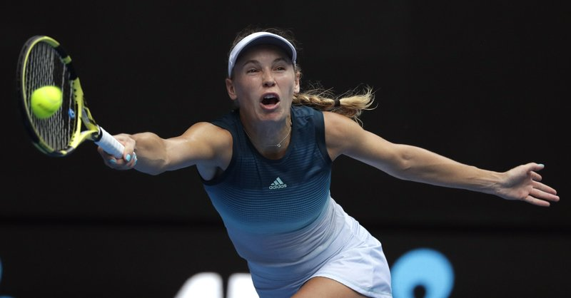 Denmark's Caroline Wozniacki makes a forehand return to Russia's Maria Sharapova during their third round match at the Australian Open tennis championships in Melbourne, Australia, Friday, Jan. (AP Photo/Kin Cheung)