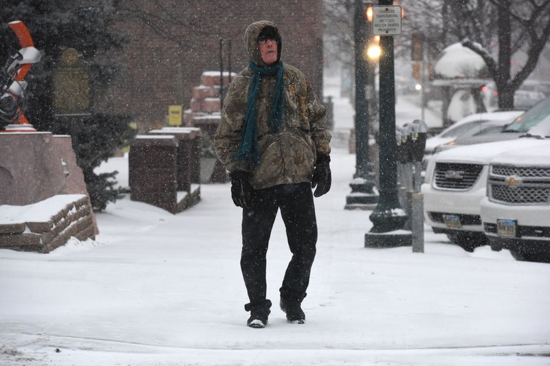A man walks downtown during a snow storm in Sioux Falls, S.D., Friday, Jan. 18, 2019. A strong winter storm system is forecast to sweep across the Midwest into New England, bringing double-digit snow accumulations and high winds. (Loren Townsley/The Argus Leader via AP)