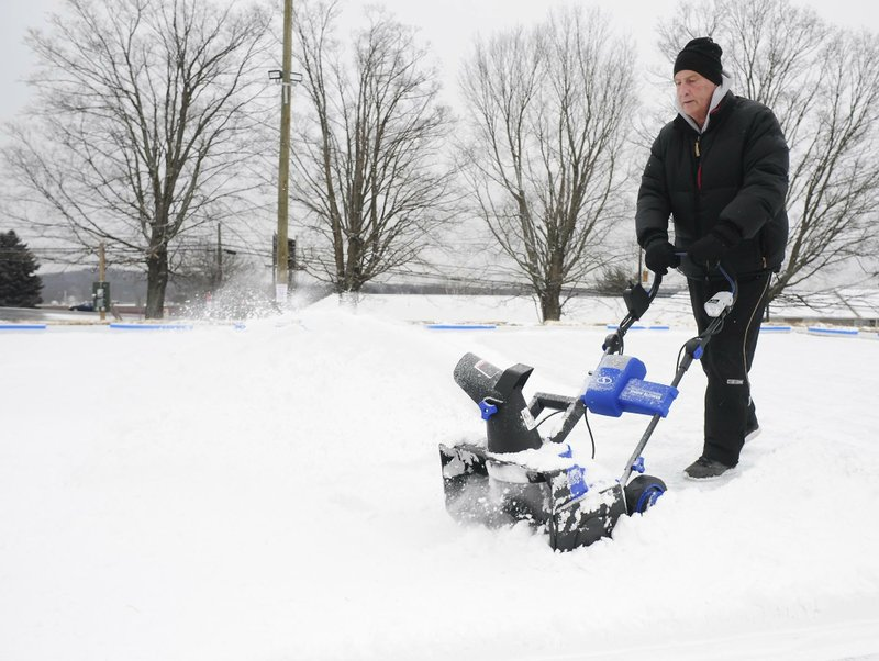 Former Wilkes Barre Scranton Penguins (AHL) head coach Glenn Patrick, uses a snow thrower to clear snow off a new ice skating rink in Dallas, Pa. (Mark Moran/The Citizens' Voice via AP)