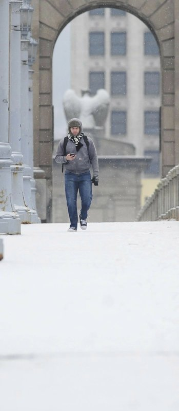 A man walks through the snow across the Market Street Bridge in Wilkes-Barre, Pa., Friday Jan. 18, 2019. (Mark Moran /The Citizens' Voice via AP)