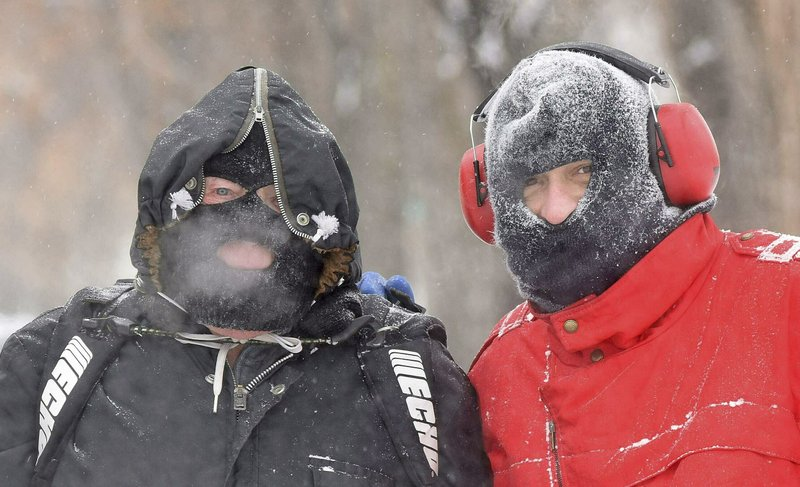 Father and son John, left, and Johnny Nagel were dressed for the cold temperatures on Friday while shoveling snow outside their north Bismarck, N. (Tom Stromme/The Bismarck Tribune via AP)