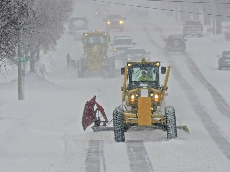 Motor graders plow Rosser Avenue as snow falls, Friday, Jan. 18, 2019, in Bismarck, N.D. (Tom Stromme/The Bismarck Tribune via AP)