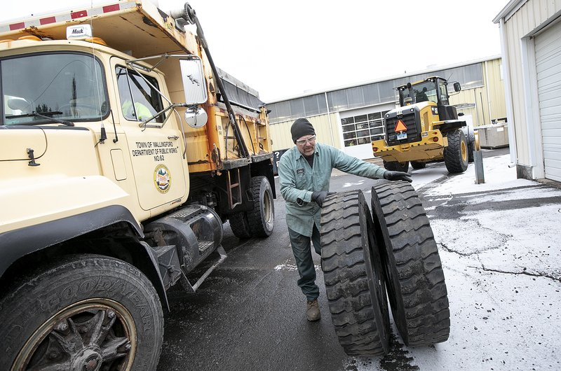 A mechanic changes out used tires as Walliingford Public Works crews prepare for the incoming storm, Fri. (Dave Zajac/Record-Journal via AP)