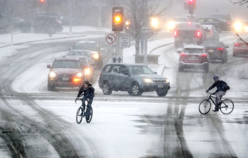 Bikers crossing Park Street at the intersection of University Ave during a late afternoon snow storm Friday, Jan. (Steve Apps/Wisconsin State Journal via AP)