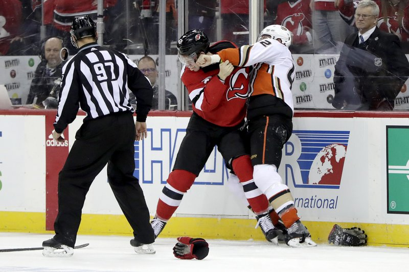 New Jersey Devils right wing Nathan Bastian, center, fights with Anaheim Ducks defenseman Josh Manson during the second period of an NHL hockey game, Saturday, Jan. (AP Photo/Julio Cortez)