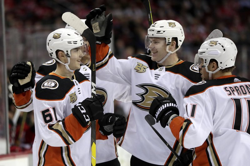 Anaheim Ducks players celebrate a goal by right wing Troy Terry, left, during the first period of an NHL hockey game against the New Jersey Devils, Saturday, Jan. (AP Photo/Julio Cortez)