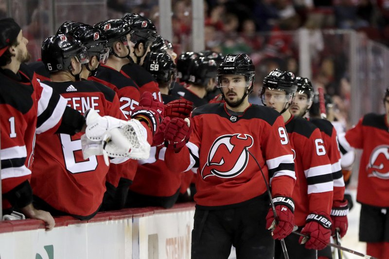 New Jersey Devils left wing Marcus Johansson, center, of Sweden, skates by his bench after scoring a goal on the Anaheim Ducks during the first period of an NHL hockey game, Saturday, Jan. (AP Photo/Julio Cortez)