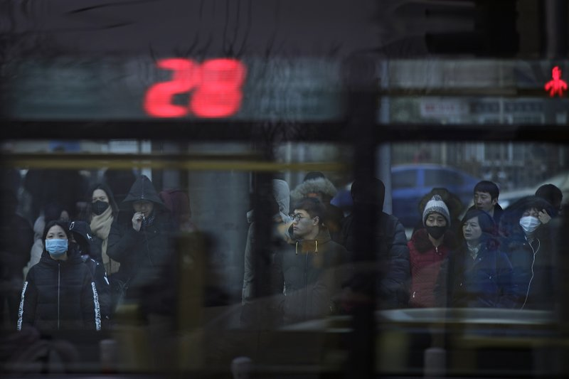 In this Jan. 14, 2019, photo, a bus passes by pedestrians at a traffic intersection in the Central Business District in Beijing. (AP Photo/Andy Wong)