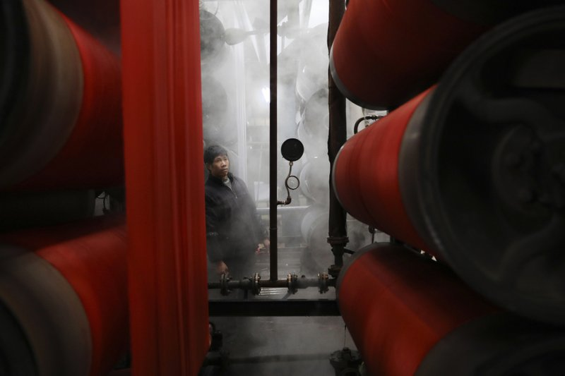 In this Jan. 1, 2019, photo, a worker monitors rolls of fabric at a dyeing factory in Hangzhou in east China's Zhejiang province. (Chinatopix via AP)