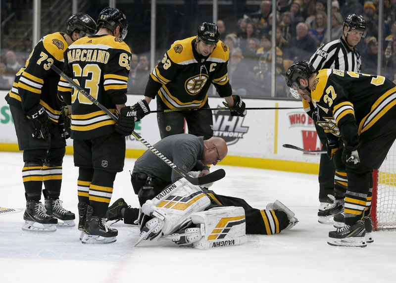 Boston Bruins goaltender Tuukka Rask (40) is attended to by medical personnel as his teammates look on after taking a hit on a goal by New York Rangers center Filip Chytil during the first period of an NHL hockey game, Saturday, Jan. (AP Photo/Mary Schwalm)