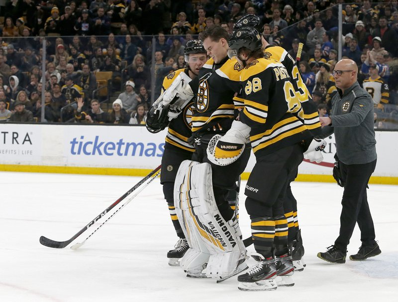 Boston Bruins goaltender Tuukka Rask (40) is helped off the ice after taking a hit on a goal by New York Rangers center Filip Chytil during the first period of an NHL hockey game, Saturday, Jan. (AP Photo/Mary Schwalm)