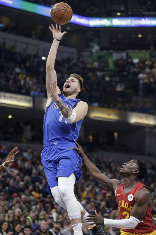Dallas Mavericks guard Luka Doncic, left, shoots in front of Indiana Pacers guard Darren Collison during the first half of an NBA basketball game in Indianapolis, Saturday, Jan. (AP Photo/AJ Mast)