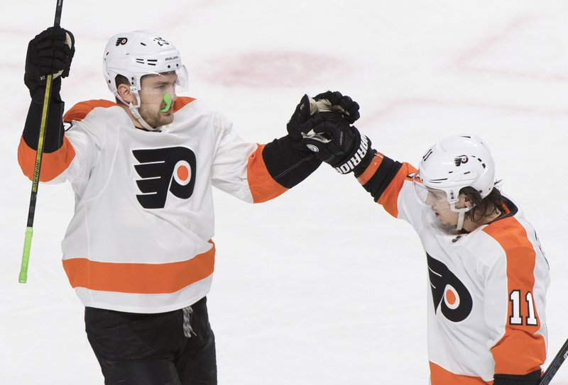 Philadelphia Flyers' James van Riemsdyk, left, celebrates with Travis Konecny (11) after scoring during the second period of an NHL hockey game in Montreal, Saturday, Jan. (Graham Hughes/The Canadian Press via AP)