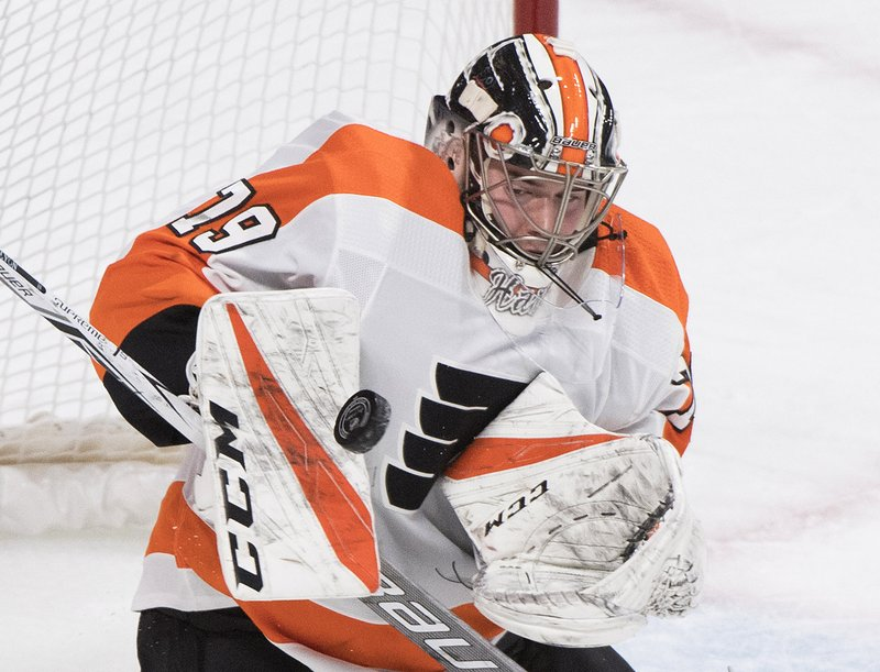 Philadelphia Flyers goaltender Carter Hart makes a save against the Montreal Canadiens during the first period of an NHL hockey game in Montreal, Saturday, Jan. (Graham Hughes/The Canadian Press via AP)