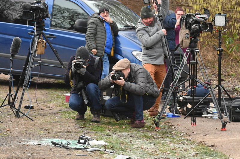 News media film broken glass and car parts on the road side near to the Sandringham Estate, England, where Prince Philip was involved in a road accident Thursday while he was driving, Friday Jan. (John Stillwell/PA via AP)