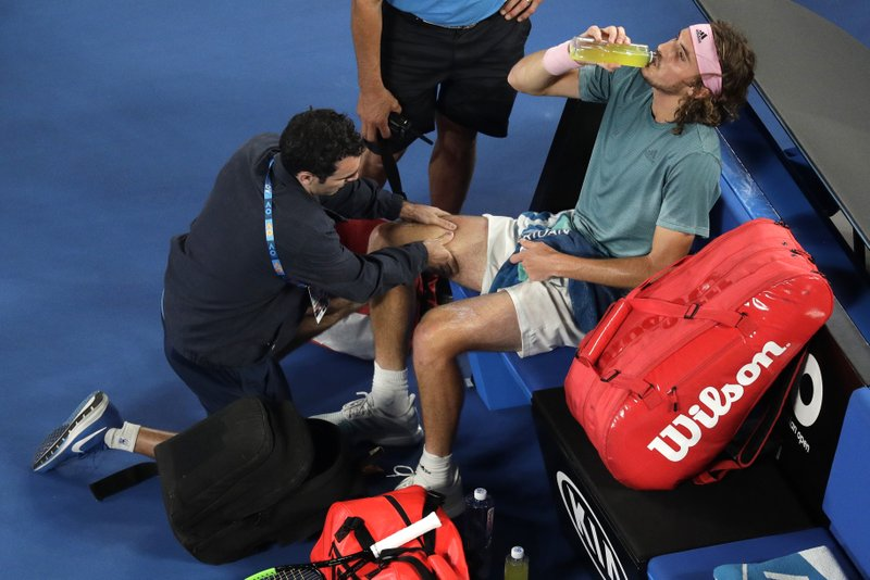 Greece's Stefanos Tsitsipas receives treatment from a trainer during his fourth round match against Switzerland's Roger Federer at the Australian Open tennis championships in Melbourne, Australia, Sunday, Jan. (AP Photo/Kin Cheung)