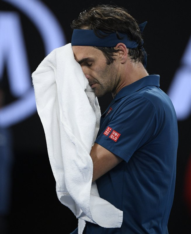 Switzerland's Roger Federer wipes the sweat from his face during his fourth round match against Greece's Stefanos Tsitsipas at the Australian Open tennis championships in Melbourne, Australia, Sunday, Jan. (AP Photo/Andy Brownbill)