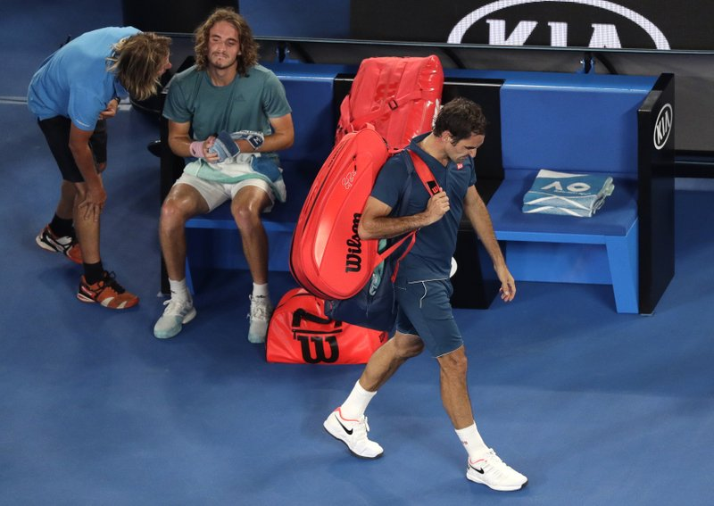 Switzerland's Roger Federer, right, leaves Rod Laver Arena after losing his fourth round match to Greece's Stefanos Tsitsipas at the Australian Open tennis championships in Melbourne, Australia, Sunday, Jan. (AP Photo/Kin Cheung)