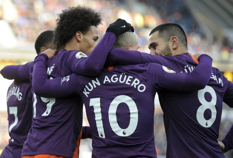 Manchester City's Leroy Sane, second from left, celebrates with his teammates Raheem Sterling, left, Sergio Aguero and Ilkay Gundogan, after scoring the third goal for his team, during the English Premier League soccer match between Huddersfield Town and Manchester City at John Smith's stadium in Huddersfield, England, Sunday, Jan. (AP Photo/Rui Vieira)