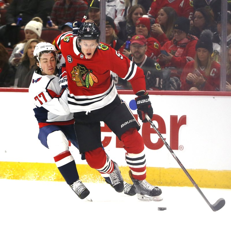 Washington Capitals right wing T.J. Oshie (77) and Chicago Blackhawks defenseman Connor Murphy (5) battle for the puck during the first period of an NHL hockey game Sunday, Jan. (AP Photo Nuccio DiNuzzo)