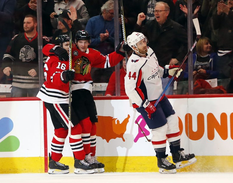 Washington Capitals defenseman Brooks Orpik (44) skates away as center Chicago Blackhawks left wing Brandon Saad, center, celebrates with center Marcus Kruger (16) after his goal during the first period of an NHL hockey game Sunday, Jan. (AP Photo Nuccio DiNuzzo)